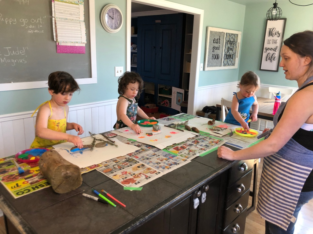 Three children and their mommy are around a kitchen island. The island is covered in newspapers that are taped down. Each has a workspace set up, including a pizza box to paint on, and the natural materials they gathered outside (including pine cones, pine needle branches, rocks, sticks, feathers and a log).