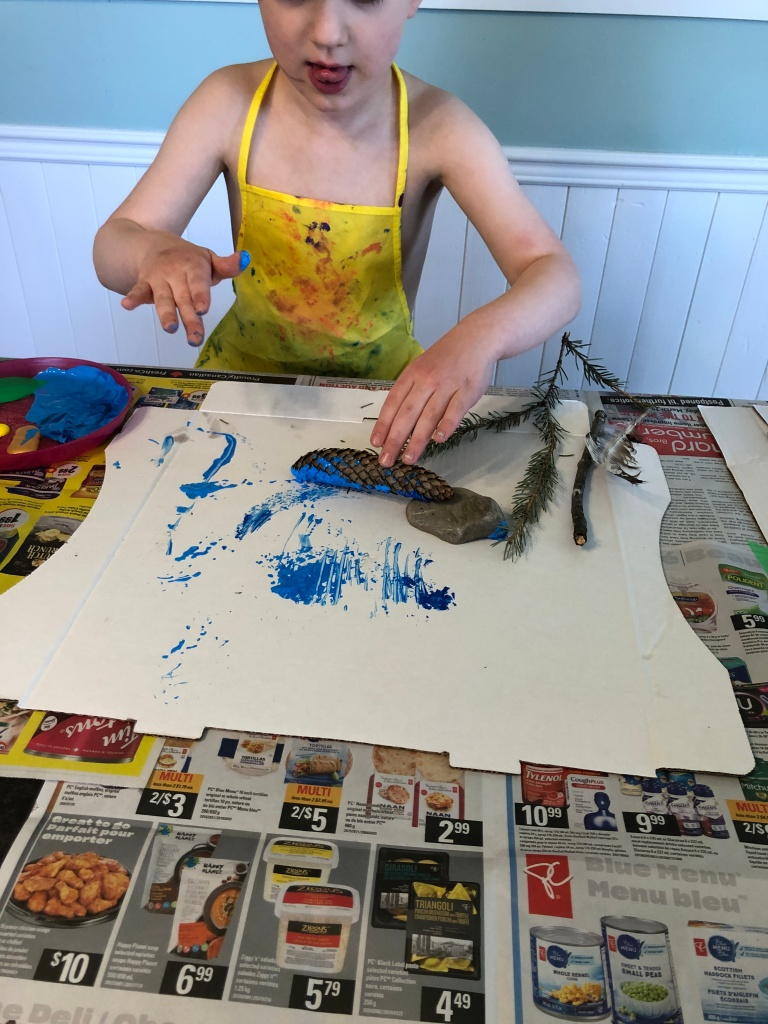 A five year old boy is rolling a pinecone, covered in blue paint, over a pizza box. He is creating lines in the paint by using the pinecone. He also has a pine needle branch, a stick, and a rock to use at his side. He is wearing a yellow apron covered in paint.