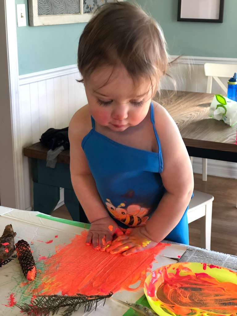 An eighteen month old boy wearing a blue painting apron has both hands pressed down into neon orange and pink paint. He is surrounded by natural materials, including a pinecone, pine needles and a rock.
