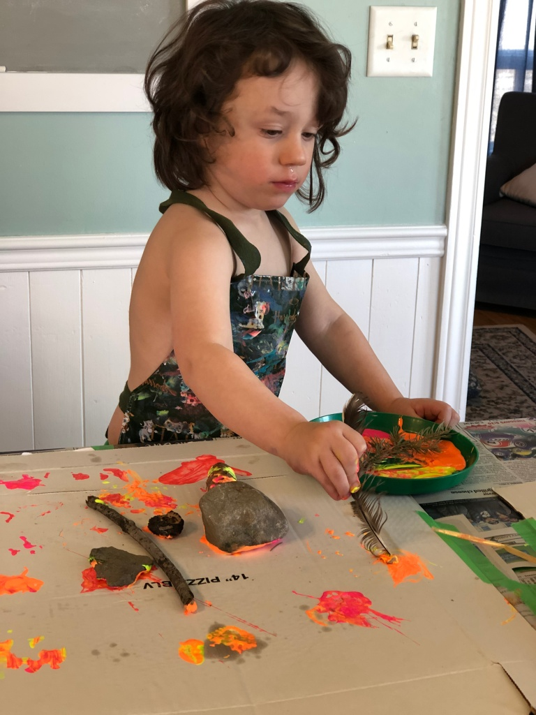 A three year old boy wearing an apron uses a feather to paint with orange paint on top of a pizza box.